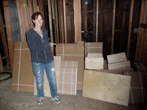 Beth points to large stack of cardboard boxes containing ready-to-assemble cabinets