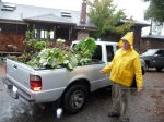 Steve in rain slicker next to truck loaded with plants