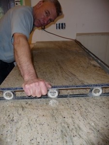 Steve checks the granite counters with a level