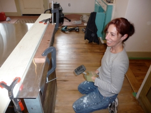 Beth uses a rubber mallet to pound down the edge of the counter
