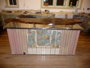 Zinc island with walnut slab bar counter and antique-wallpaper-on-beadboard accent