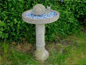cement snail sits on bed of blue marbles in a birdbath